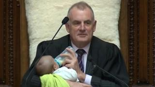 New Zealand's speaker Trevor Mallard cradles an MP's baby during a debate