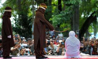 Indonesian woman being flogged in front of audience with smartphones