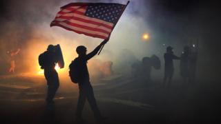 A protester waves an American flag while walking through tear gas fired by federal officers during a protest in front of the Mark O Hatfield US Courthouse in Portland, Oregon, 21 July 2020