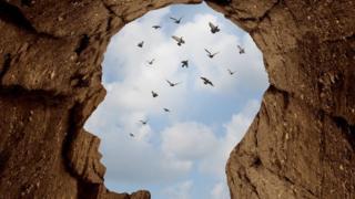Forma de cabeza en rocas con vista al cielo y pájaros
