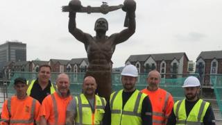 The David Pearce statue in Newport with the workers who constructed it