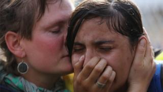 A migrant girl is comforted after being overcome by tear gas, 16 Sept