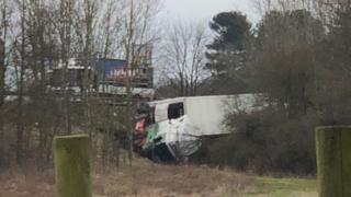 Photograph of a lorry which has left the road before coming to rest on its side