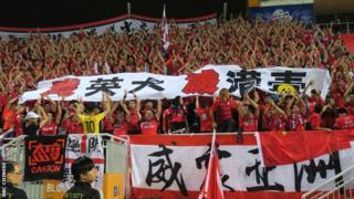 """Những cổ động viên đội Evergrande ở Quảng Châu, Trung Quốc, cầm biểu ngữ mang dòng chữ: """"Tiêu diệt những con chó Anh, xóa bỏ chất độc đòi độc lập cho Hong Kong"""" tại một trận bóng đá ở sân vận động Mong Kok tại Hong Kong, ngày 25 tháng Tư năm 2017."""
