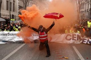 A protester holds a smoke torch during a demonstration against pension reforms in Marseille, France