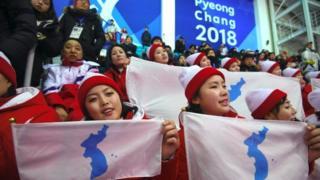 વિન્ટર ઑલિમ્પિક સમયે સંયુક્ત કોરિયાના ધ્વજ સાથે યુવતીઓ