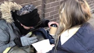 Florence giving a hot drink to a rough sleeper