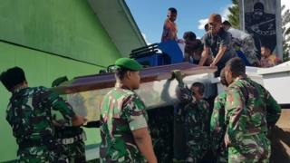 Indonesian soldiers prepare coffins for construction workers, believed to have been shot dead in Papua province on December 4, 2018