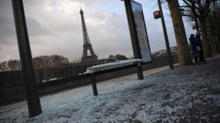 Parada con vidrios rotos y al fondo se ve la Torre Eiffel