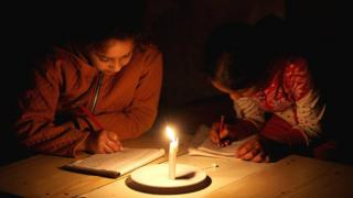 Palestinian refugee girls study by candlelight in their family's makeshift house during a power outage at Khan Younis refugee camp in the southern Gaza Strip (23 April 2017)