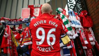 "Fan lays tribute on gate - his shirt says ""never ever forget - 96"""