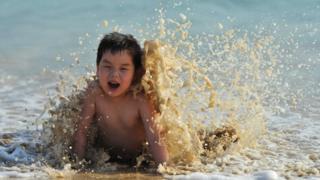 小孩到海邊玩樂。