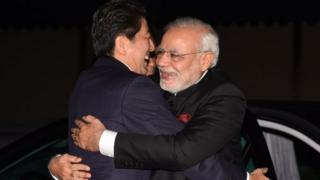 India's Prime Minister Narendra Modi (R) is embraced by his Japanese counterpart Shinzo Abe upon his arrival at the State Guest House in Kyoto.