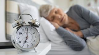 Mulher dormindo próxima a despertador