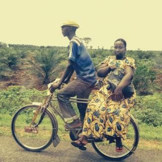 Woman balanced on the back of a bicycle in Burundi