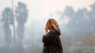 A woman reacts as the Woolsey Fire burns in Malibu, California,