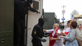 A police officer detains Belarusian opposition supporters ahead of a march in Independence Avenue, 30 August