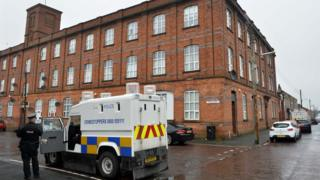 A police officer stands outside the block of flats on Victoria Street in Lurgan where the woman's body was found