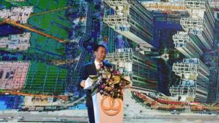 Wanda Group chairman Wang Jianlin speaks in front of an image of a real eastate development