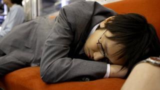 Спящий одетым на работе японец