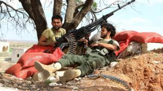 Rebel fighters rest with their weapons in Latamina village, northern Hama countryside (5 March 2016)