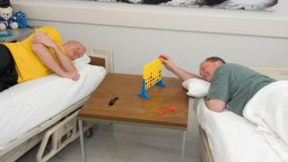 Dois homens deitados em camas durante realização de estudo científico