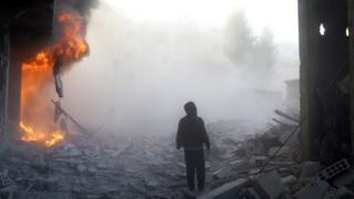 A man walks near a building on fire following a reported air strike by government forces in the rebel-held region of Eastern Ghouta, on the outskirts of the Syrian capital Damascus