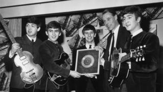 George Martin with the Beatles receiving their first silver disc