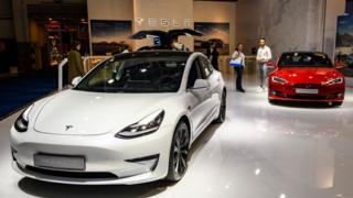 A white Tesla model 3 is seen on the left and a Red Model S on the right on a show floor