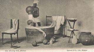A postcard showing an Indian domestic help pouring water over a white man while he bathes in a tub.
