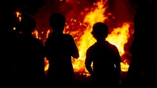 Children watching a bonfire.