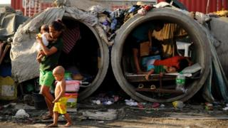 Families live in concrete pipes used as makeshift dwellings along a street in Manila on March 22, 2016. Roughly one quarter of the nation's 100 million people live in poverty, which is defined as surviving on about one US dollar a day, according to government data.