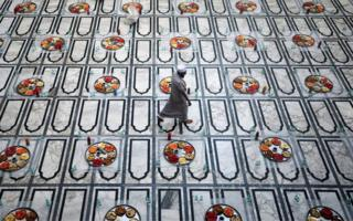 A Muslim man walks through the mosque where laid out on the floor are lots of colourful dishes