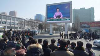 North Koreans watch a huge screen broadcasting an official announcement by a TV news presenter