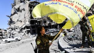 Fighter waves a Syrian Democratic Forces flag in Raqqa on 17 October 2017