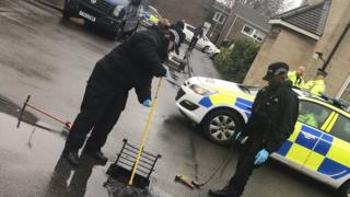Police examine a drain in Corby old village