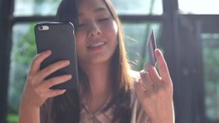 Jovem com celular e cartão