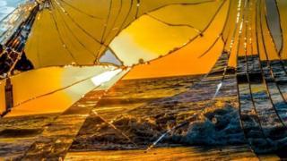 Un espejo roto refleja la imagen de una playa al atardecer.