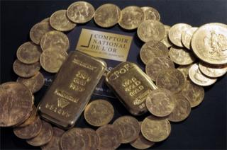 A picture showing gold bars and coins on a table at the Comptoir National de l'Or, a shop that buys, sells and estimates gold and jewellery in Paris.