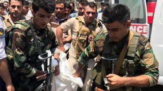 قوات الأمن تحمل جثة أحد المهاجمين