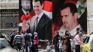 Syrians walk past billboards of Bashar al-Assad and his father in Damascus (file photo)