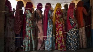 Indian women wait to vote at a polling station on April 17, 2014