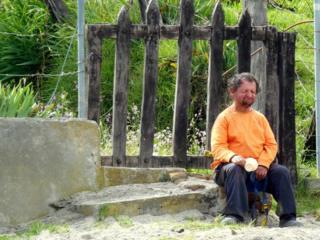 Hombre de camisa naranja espera sentado en la carretera