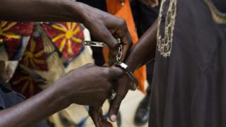 """Police remove the handcuffs from political prisoners arriving for their hearing at Gambia""""s supreme court in Banjul, Monday, Dec. 5, 2016. They had been arrested in April 2016 after they took part in a peaceful demonstration and sentenced to three years in prison. The appeals court ordered their release on bail, just days after strongman ruler Yahya Jammeh agreed to step aside after losing the presidential election to Adama Barrow"""