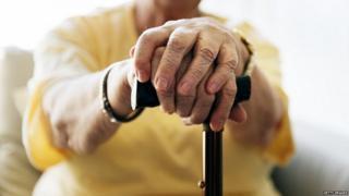 Elderly woman holding walking stick