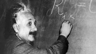 Albert Einstein writing on a blackboard
