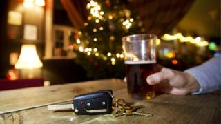 A man drinks a pint of beer while his car keys sit on a bar top