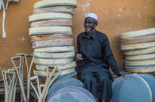 A man sits selling sieves
