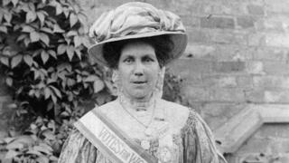 Alice Hawkins with a Votes for Women sash and poster