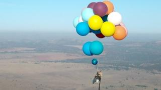 Tom Morgan from di Bristol-based company The Adventurists, dey fly inside chair wey dem tie with big party balloons near Johannesburg, South Africa on 20/10/2017